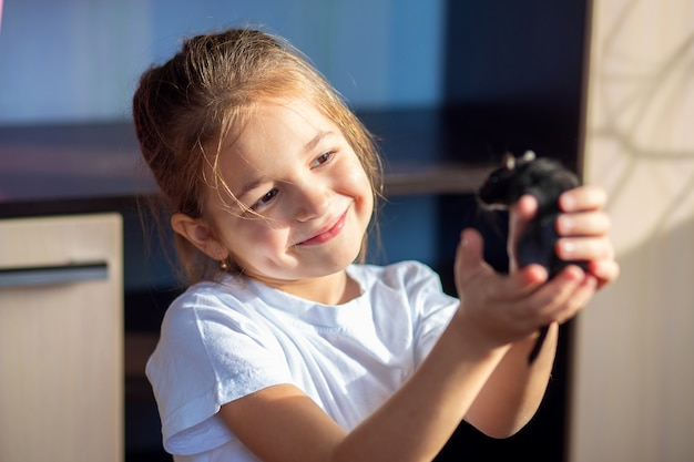 白いtシャツの女の子がモンゴルのスナネズミを手に持って抱擁