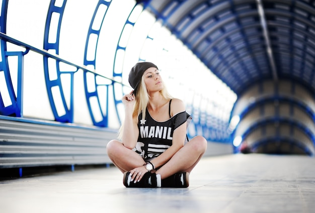 大きなtシャツのヒップホップスタイルと青いトンネルに座っているキャップの少女