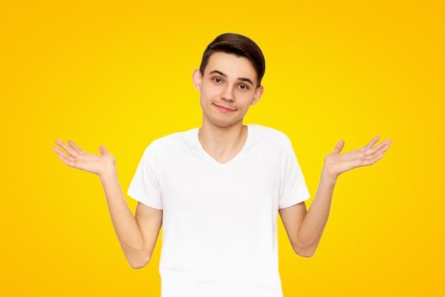 白いtシャツの男は、黄色に分離された答えを知らない、ジェスチャー、ジェスチャーを示しています