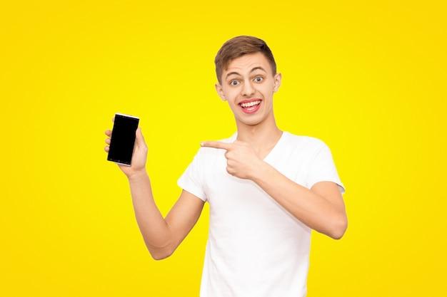 白いtシャツを着た男は黄色の背景に分離された携帯電話を宣伝します。