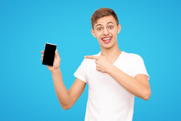白いtシャツを着た男は青い背景に分離された携帯電話を宣伝します。