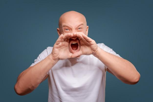 白いtシャツを着てハンサムな幸せな男、大声で話す、青い背景で隔離