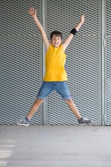 黄色のtシャツを着ているとジャンプの若いティーン