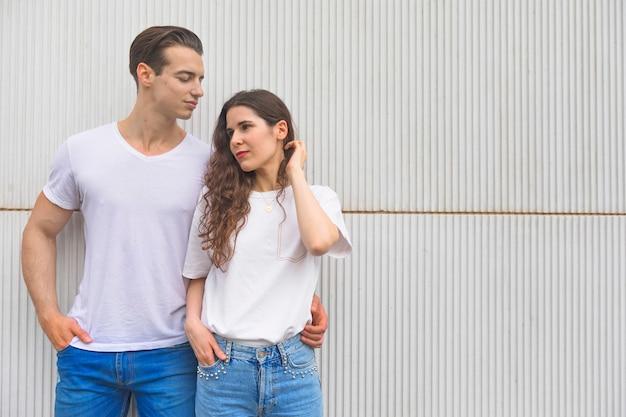 ジーンズとtシャツを着てポーズ美しいカップル