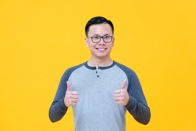 親指をあきらめて笑みを浮かべてカジュアルなtシャツで楽観的なアジア人