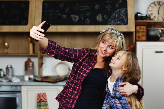 ママと娘は同じtシャツの居心地の良いキッチンに立って自分自身のセルフを取る