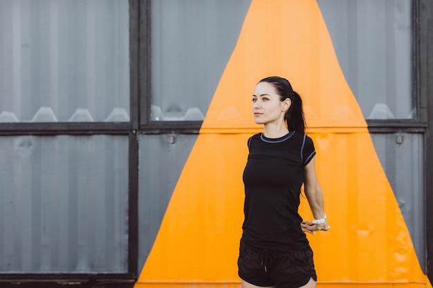 黒のtシャツとショートパンツを着て、黄色の灰色の壁で実行する前にウォーミングアップする女の子