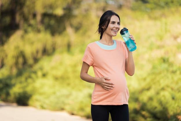 ピンクのtシャツを着た女性が公園を歩いています。