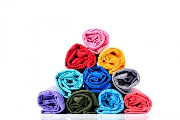 ロールのカラフルな白い背景に分離されたピラミッド形に作られた綿のtシャツ。