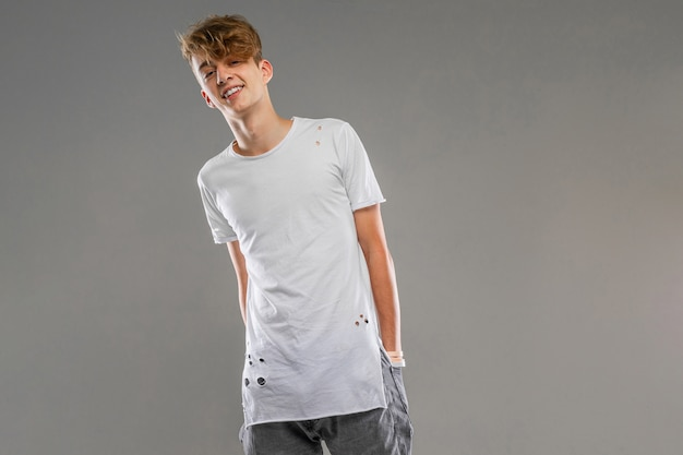 白いtシャツを着た白人の男が灰色の壁のポケットに手を入れた