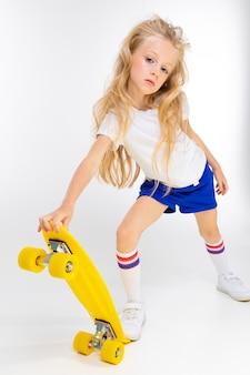 スポーツショートパンツ、tシャツ、白い壁に黄色のスケートボードとジムの靴でかわいいブロンディの女の子