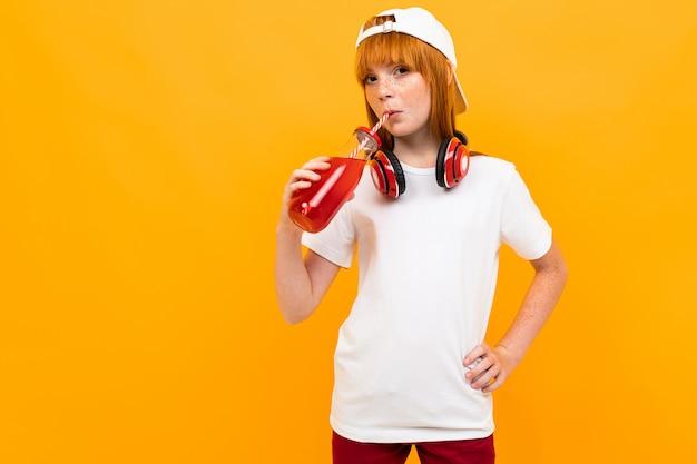 黄色の背景に分離された白い帽子笑顔とドリンクジュースと白いtシャツに赤い髪の幸せな女の子