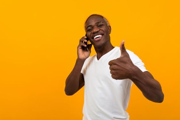 きれいな黄色のスタジオの背景に電話で話している白いtシャツで陽気な笑顔のアフリカ人