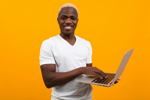 オレンジ色の背景にラップトップを備えた白いtシャツを着た美しい白雪姫の笑顔のブラックアメリカン