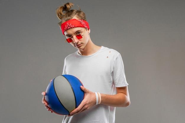 白いtシャツ、バンダナとパン、頭にパン、灰色の壁の背景にバスケットボールの赤いサングラスの男