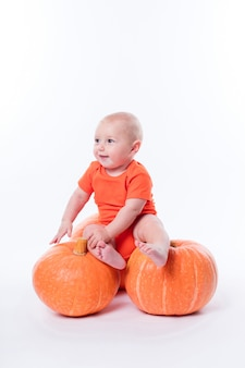 オレンジ色のtシャツに座っている美しい赤ちゃん