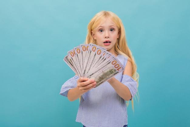 長いブロンドの髪を持つ青いtシャツの白人少女の肖像画は青に分離されたお金を保持します