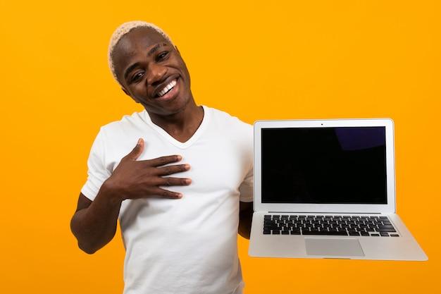 白いtシャツで美しい笑顔でハンサムなアフリカ人は黄色のスタジオでモックアップでポータブルワイヤレスコンピューターを保持します