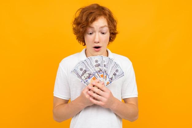 黄色の彼の手で紙幣のファンを保持している白いtシャツで幸せな驚いてティーンエイジャーの男の子