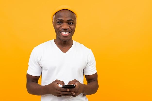 白いtシャツでアメリカ人の笑顔は黄色の携帯電話を保持しています。