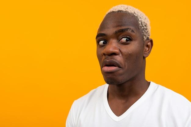 白いtシャツを着たカリスマ的なアフリカ人はコピースペースと黄色の側に驚いて見える