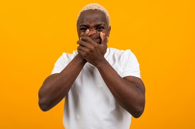 白いtシャツでハンサムなアメリカ人の男は分離された黄色の彼の手で彼の口を短所します。