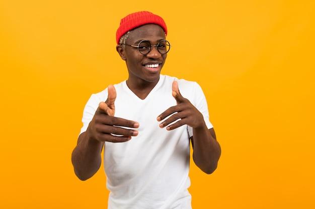 白いtシャツに身を包んだ陽気なスタイリッシュな黒人アフリカ人は彼の手を示しています