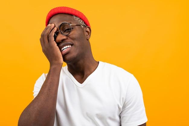 コピースペースと黄色の彼の手で彼の顔を覆って笑みを浮かべて白いtシャツで陽気な黒アメリカ人