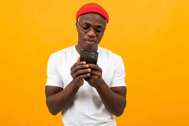 白いtシャツを着たハンサムなアフリカ人が黄色の電話でソーシャルネットワークで通信します。