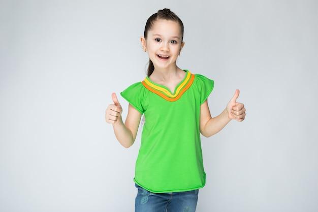 緑のtシャツとブルージーンズの女の子