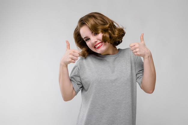 灰色の壁に灰色のtシャツの魅力的な若い女の子。