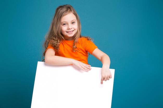 茶色の髪のtシャツでかわいい女の子がきれいな紙を保持します。
