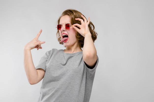 灰色の背景に灰色のtシャツの魅力的な若い女の子。赤い四角いメガネの女の子。女の子はロッカーヤギを示しています