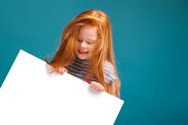 長い髪のtシャツのかわいい美しさの少女はきれいな紙を保持します。