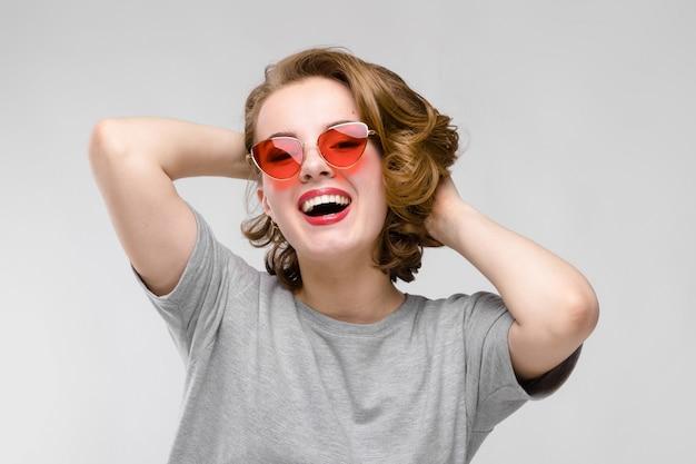 灰色の背景に灰色のtシャツの魅力的な若い女の子。赤いメガネで幸せな女の子。女の子は頭の後ろに手を置いた