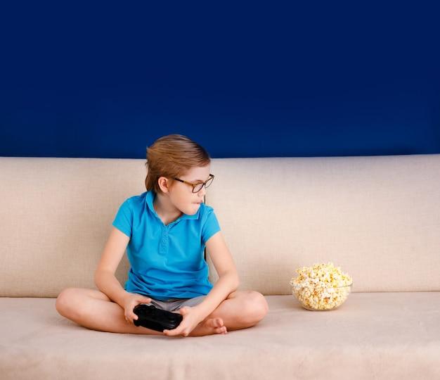 青いtシャツとソファに座って、自宅でゲームパッドで遊んでいる大きなメガネの少年。青色の背景とテキスト用の空き容量。家庭と遠隔教育