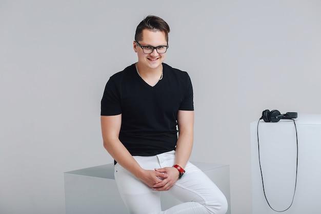 黒いtシャツ、白いズボン、メガネの若いヒップスターがチューバに座っています。