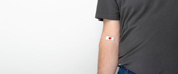 献血。灰色の背景に血を与えた後、赤いハートのパッチでテープで留められた灰色のtシャツの手の男。