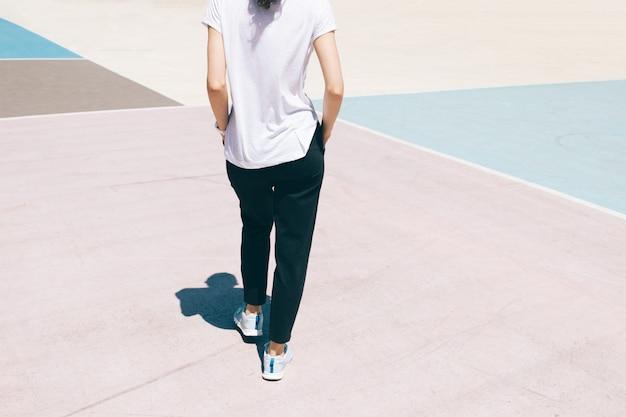 スポーツパンツ、tシャツ、スニーカーが遊び場の上を歩く若い女性の画像をトリミング