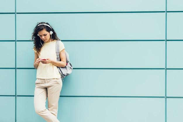 青い壁の表面に立っていると携帯電話とヘッドフォンで音楽を聴く黄色のtシャツの女の子