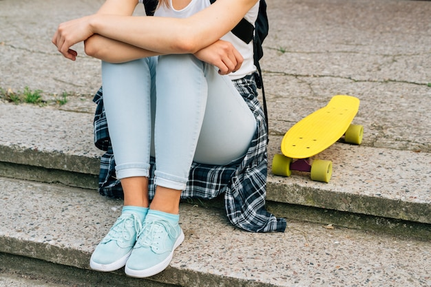 ジーンズ、スニーカー、屋外の彼女の黄色のスケートボードの横にある階段に座っているtシャツの女の子
