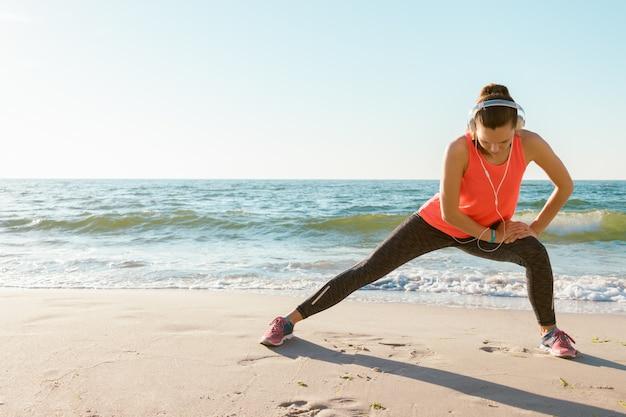 赤のtシャツのスリムな運動少女は、日差しの中でビーチで午前中にストレッチされています