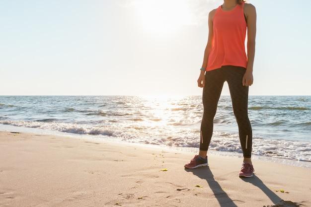 ジョギングする前に朝の日差しの中でビーチに立っている袖とスニーカーなしの赤いtシャツのアスレチック女