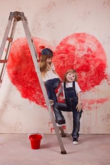 男の子と女の子のジーンズと白いtシャツ、絵筆とバケツの梯子の上に立つ
