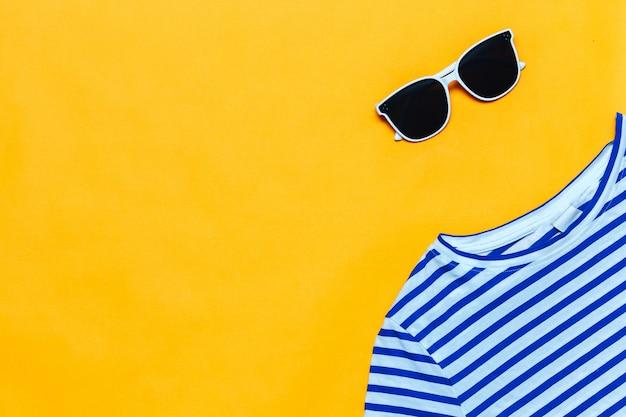 明るいブルーのストライプのtシャツと白いサングラス