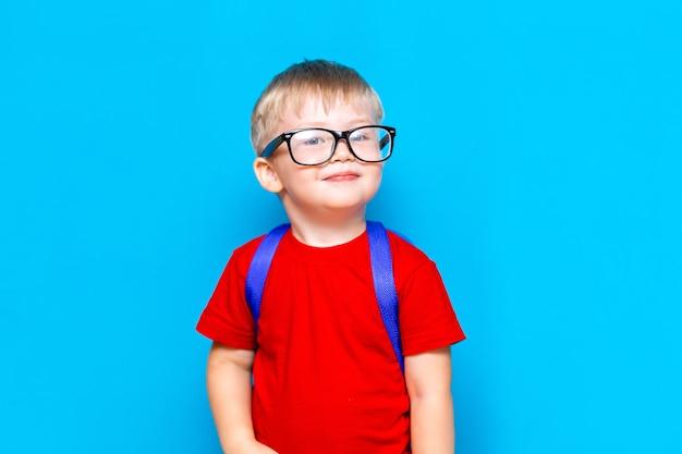 メガネの赤いtシャツで幸せな微笑む少年は初めて学校に行く予定です。ランドセルを持つ子供。学校に戻る