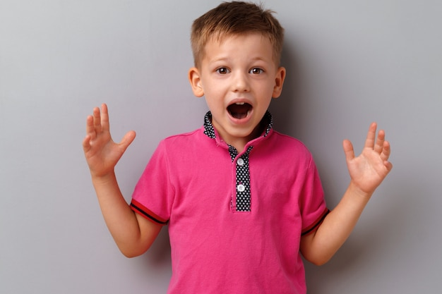 小さな男の子は灰色の背景にピンクのtシャツを着て驚いてショックを受けた