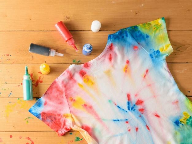 茶色の木製のテーブルに絞り染めのスタイルで描かれたtシャツ。