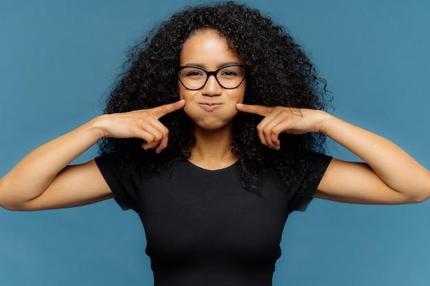 面白い陽気な女性が頬を吹く、両方の人差し指で触れる、黒のカジュアルなtシャツを着る
