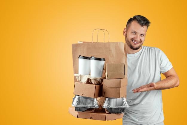 黄色の背景に分離されたファーストフードの注文を与える明るいtシャツの男